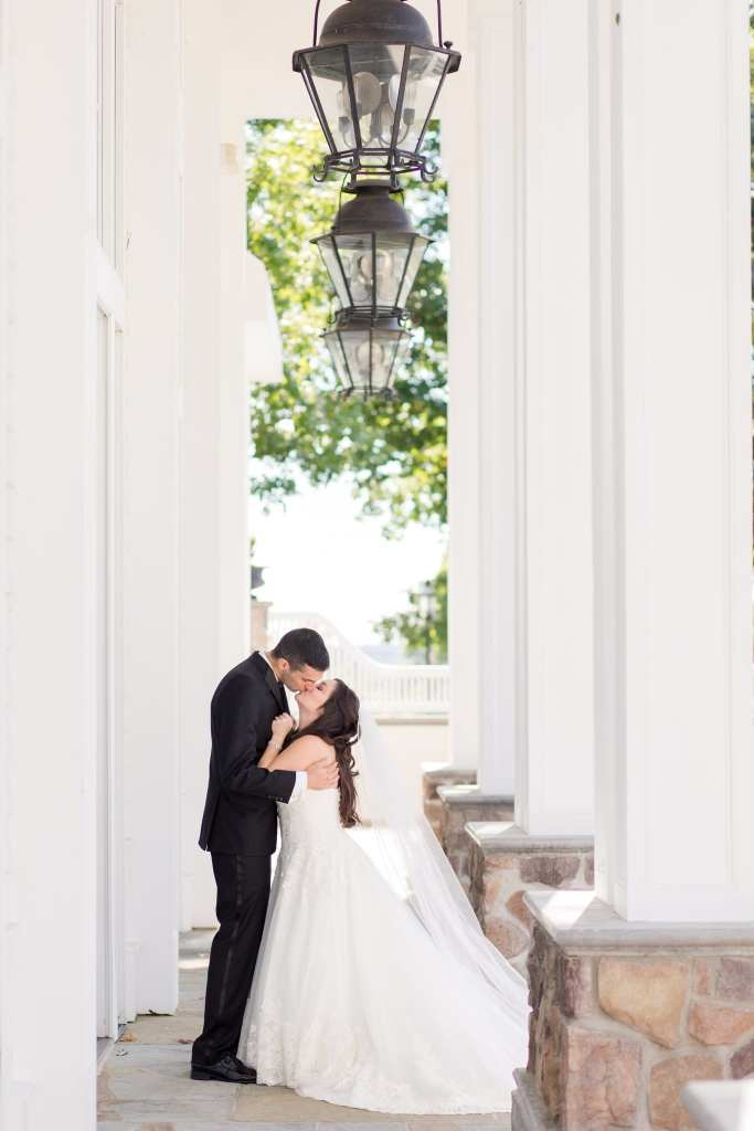 The bride and groom kiss outside the grand ballroom at the Ryland Inn in these Ryland Inn Wedding Photos