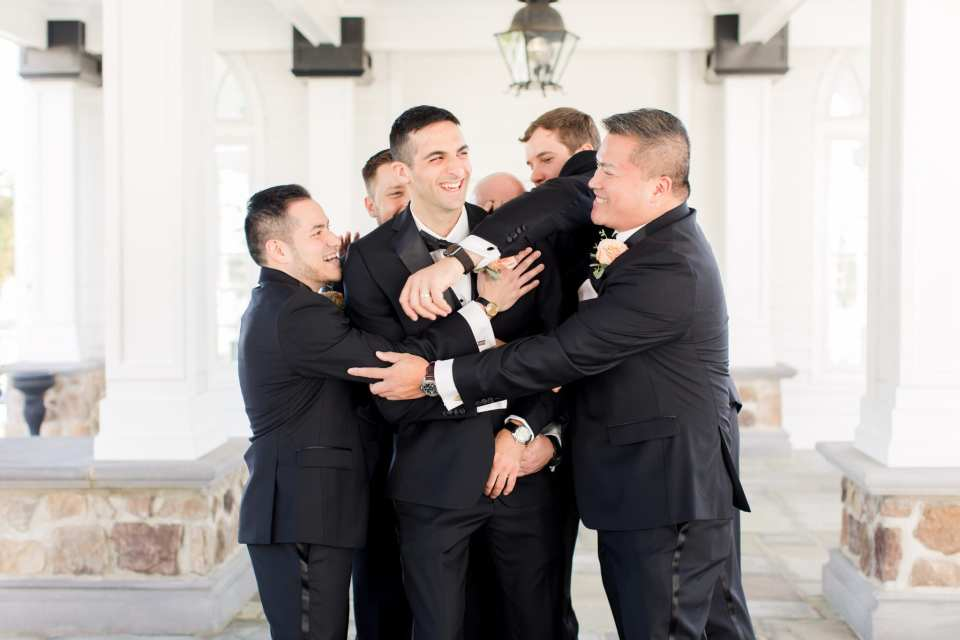 The groom and his groomsmen laugh and have a good time in this fun shot
