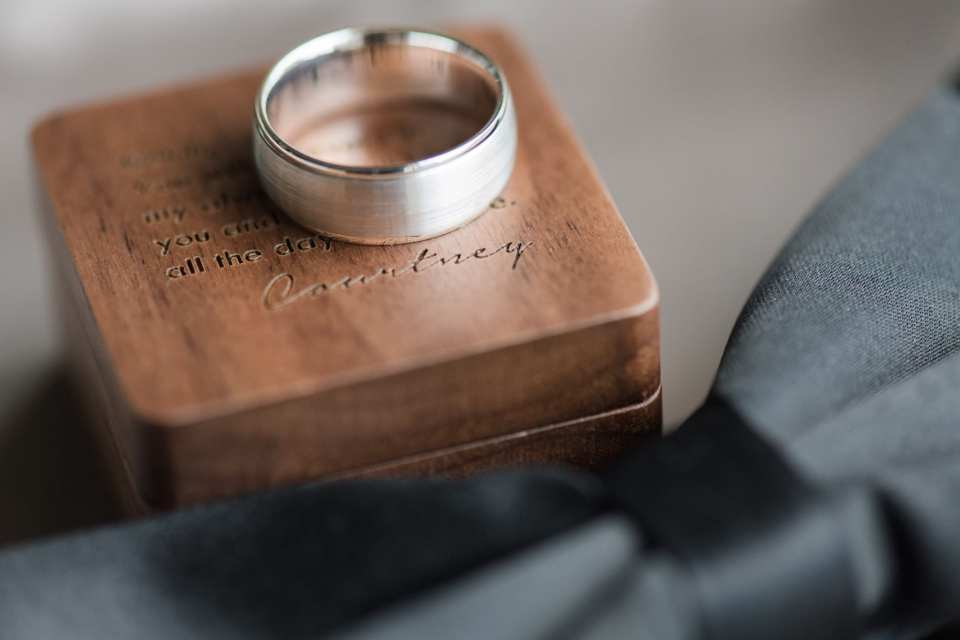 The grooms brushed platinum wedding band by Gabriel & Co on display on top of a custom engraved box with a message from the bride