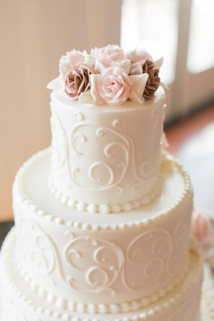 Close up of the top of the four tier embossed white wedding cake accented with beige and pink roses by Palermo's Bakery
