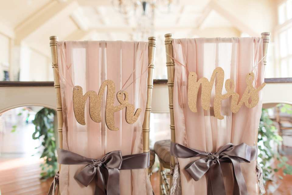 Wedding details: Sweetheart table chivari chairs draped with chiffon fabric, tied with satin bow and adorned with custom glitter Mr and Mrs signage