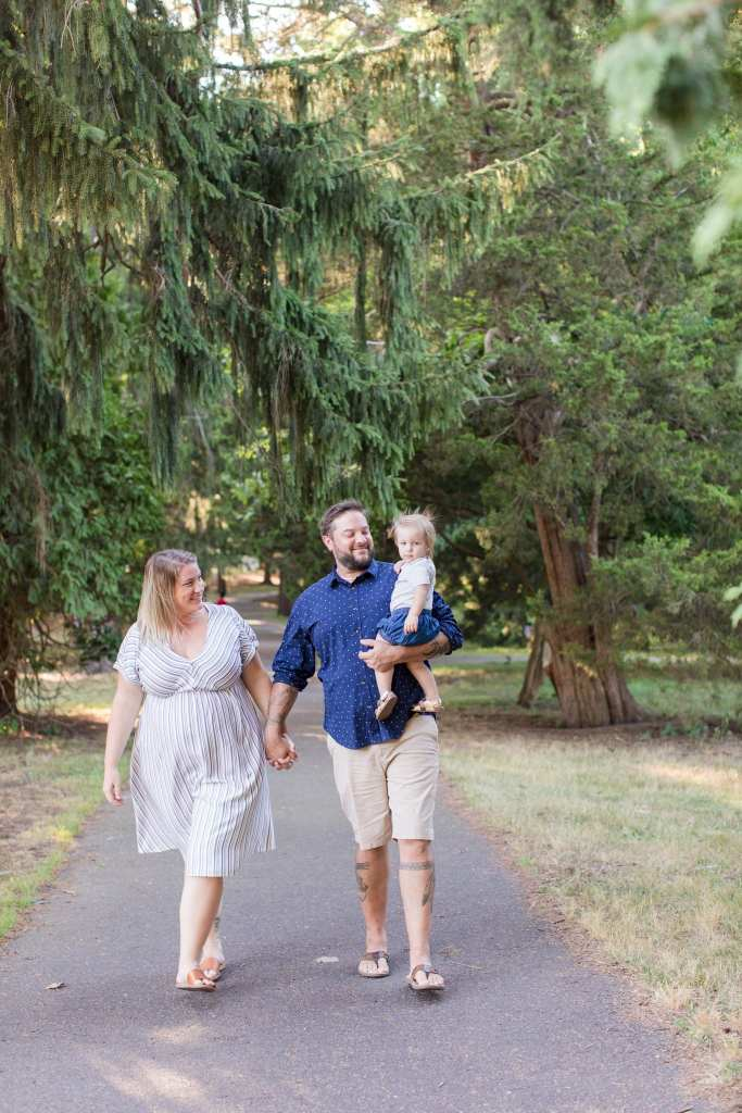 Family of three, mom and dad holding hands as dad carries child, walking towards photographer outdoors on tree lined path in these front-line healthcare worker photos
