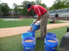 Groundskeeper Scout Carter of Blackshear, GA fills calzyme clay into buckets. The clay is used to re-sod the infield grass. (April 15th) Photo Credit: Jaylon Thompson, Multiplatform news