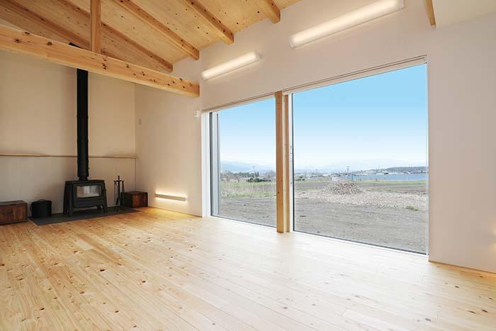 珪藻土の白壁のやわからな質感に、無垢材の美しさが際立つリビングルーム。現しの梁や薪ストーブが信州というロケーションにしっくりと馴染む