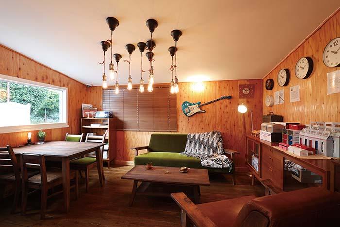 写真は店内の様子。ヴィンテージ感が漂うソファ・テーブル・ダイニングセットは、愛知県の家具メーカー「吉桂」のウイスキーオークシリーズで、国産ウイスキーの樽として使われた材を家具に再利用したもの。左角の棚と右壁沿いのサイドボードは同じく愛知県に本社を置く国内家具業界の最大手「カリモク」の、創業当時の復刻シリーズ「カリモク60」から。異なるブランドの家具や雑貨が心地よく調和するモダンでどこかレトロな店内は、インテリアコーディネーターとして評判の高い店長のセンスが際立つ空間となっている。下はアメリカンテイスト漂うショップ外観