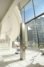 吹き抜けにレイアウトされた螺旋階段が印象的。広く切り取られた窓の外には、東京の空と美しい都心の風景が広がる