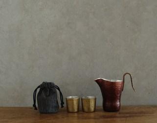 「伊藤祐嗣 銅のちろり 旅酒盃」銅のちろりは外側は漆を焼き付け内側は錫引き。真鍮の旅酒盃も同様の仕様で、古裂の巾着袋がセットになっている