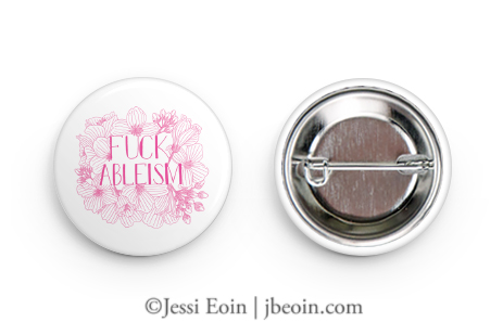 """An image of a white pinback button with a pink illustration of flowers and text that reads """"Fuck Ableism"""" in all caps."""