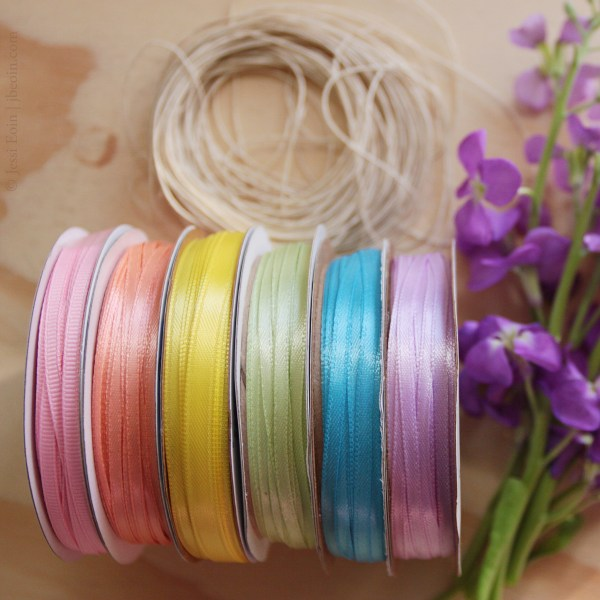 A styled photo of several spools of colorful ribbon and twine. From left to right, the colors are pink, peachy orange, yellow, green, blue, and purple. The twine is a beige color. The photo is styled with purple stock flowers.