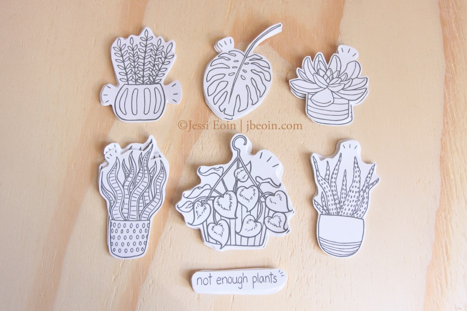 "A photo of the 8 hand cut, die cut stickers from the Plant Babies sticker set. There are 6 different species, five of which (a ZZ Plant, a succulent, a snake plant, an aloe vera plant, and a pothos plant) are potted in different pots and one of which is a giant Monstera leaf. There is also a sticker that has text on it that reads, ""Not enough plants."""