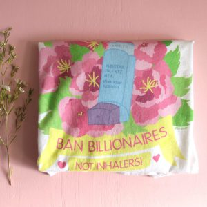 """A photo of a folded white t-shirt with a colorful floral design behind a blue and purple inhaler that has the label """"Albuterol Sulfate HFA Inhalation Aerosol"""" and the expiration date """"Aug 20"""" on it. The floral design shows several big, pink peonies with yellow stamens and bright green leaves. Underneath the design is a yellow banner with pink text on it that reads, """"Ban Billionaires, Not Inhalers!"""" in all caps and two pink hearts on either side."""