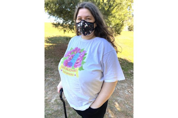A photo of Jessi modeling the shirt outdoors, smiling at the viewer. They are visibly disabled, wearing a unicorn printed Vogmask and using a black cane that pairs well with their black pants. The shirt's colors are vibrant, and the shirt fits well and slightly loose, without being or looking too baggy. A white tank top's straps are just barely visible under the shirt.
