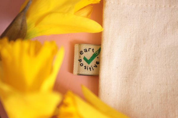 """A close up photo of the small tag on the outside of the bag that reads, """"Earth Positive"""" with a green check. The tag is surrounded by a few yellow daffodils."""