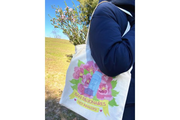 A photo of a tall person wearing a thick blue jacket modeling the bag outdoors. The bag is over their shoulder and has a bunch of fresh flowers in it. The size of the bag is fairly large and goes from about mid-back on the model to just around their butt.