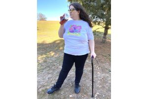 A photo of Jessi modeling the shirt outdoors while drinking strawberry bubble tea with a plastic straw and looking off in the distance. They are visibly disabled, wearing blue light blocking glasses and using a black cane that pairs well with their black pants and shoes. The shirt's colors are vibrant, and the shirt fits well without being or looking restrictive. A white tank top's straps are just barely visible under the shirt.