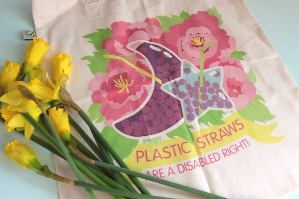 """A photo of a pale beige, cotton tote bag with a bunch of bright yellow daffodils tossed slightly over it. The art on the bag shows a colorful floral design behind some whimsical, moon and star shaped bubble tea drinks with flexible plastic straws in them. The moon shaped drink is purple with red-purple bubbles and a yellow straw, and the star shaped one is a pale blue with purple bubbles a green straw. The floral design shows several big, pink peonies with yellow stamens and bright green leaves. Underneath the design is a yellow banner with pink text on it that reads, """"Plastic Straws Are a Disabled Right!"""" in all caps."""