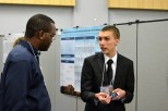 Patrick Messimer mesmerizes Delon Roberts with his presentation on a high-functioning robotic hand.