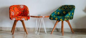 Two décor chairs with a small table between them.