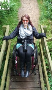 Jo Southall on a narrow wooden bridge in her purple wheelchair.