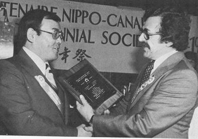 4. 1977年、萬蔵の孫テッド鶴雄は、ケベック州労働移省民大臣ジャッキーから日系百年記念の盾を受け取った。
