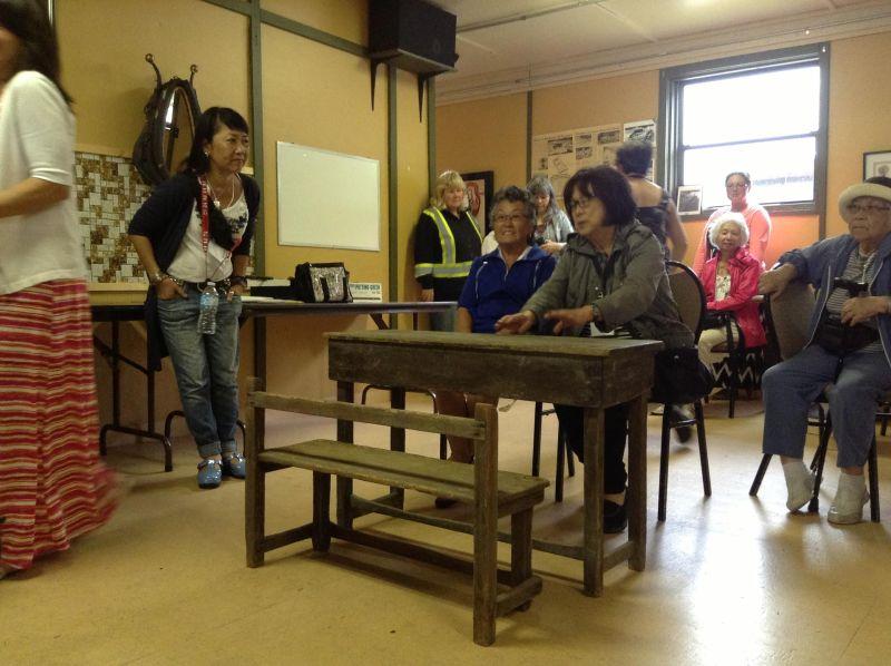 強制収容時はアパートだったタシメの建物で、当時の小学校の机と椅子をなつかしむ参加者達。今はコミュニティホールとして使われている。