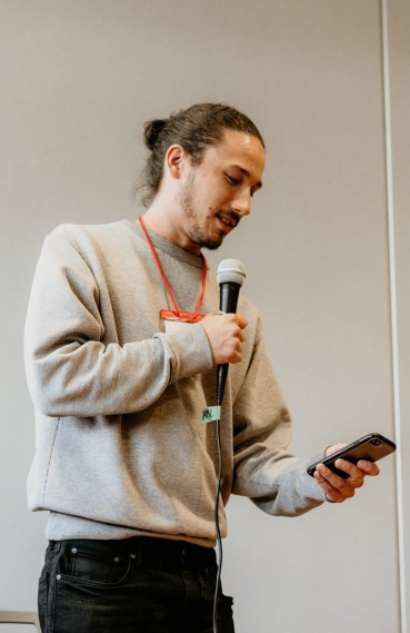 Sho, visiting from Los Angeles, CA, shares poetry during an open mic event after lunch.