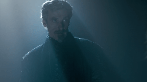 Cardinal Richelieu stands in a dark room, looking evil and sceptical.