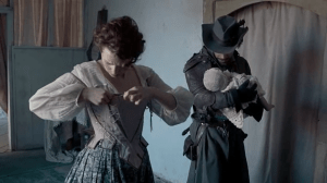 Constance laces up her bodice in the foreground while in the background Aramis holds a baby.