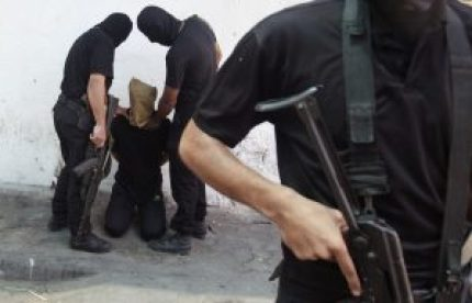 Hamas militants grab a Palestinian suspected of collaborating with Israel in Gaza City