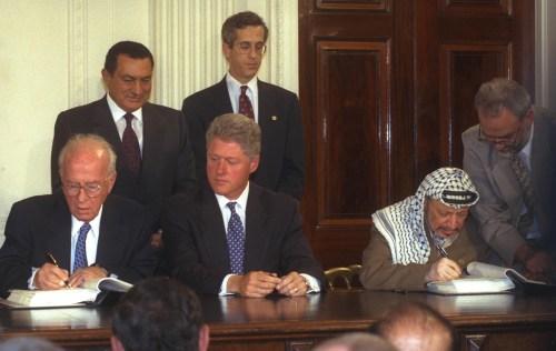 Le Premier ministre israélien Yitzhak Rabin et Yasser Arafat de l'OLP signent l'accord intérimaire d'Oslo de 1995. Le président Clinton, le président égyptien Moubarak et (cachés de la vue) le roi jordanien Hussein