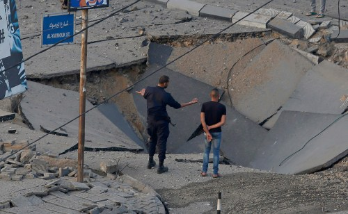 People stand on a destroyed street after an Israeli air strike hit