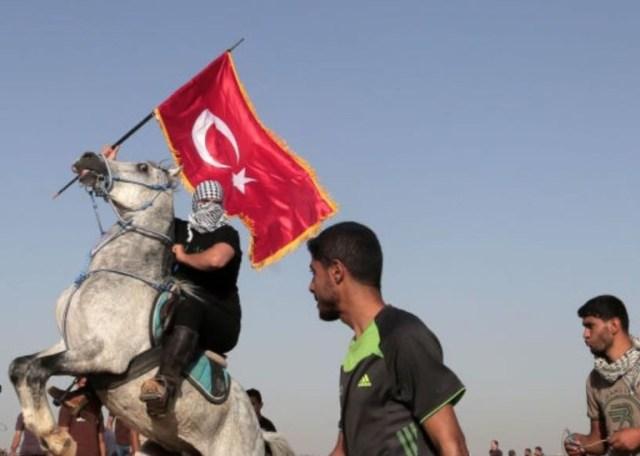 """תצלום: מפגין בעזה, רוכב על סוס, מחזיק בדגל תורכי במהלך הפגנת """"צעדת המיליון של ירושלים"""" ב- 8 ביוני 2018, לציון יום ה""""נכסה"""" ויום אל-קודס (יום ירושלים) בגבול עזה-ישראל."""