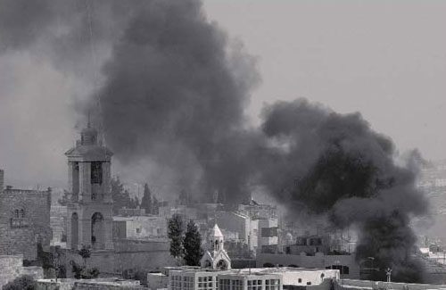 Black smoke billows over the Church of the Nativity compound in the West Bank town of Bethlehem on April 11, 2002, after the church was seized by a joint unit of Fatah and Hamas. The clergy were taken hostage and the interior was desecrated. (AP Photo/Peter Dejong) - Defending Israel's Legal Rights to Jerusalem