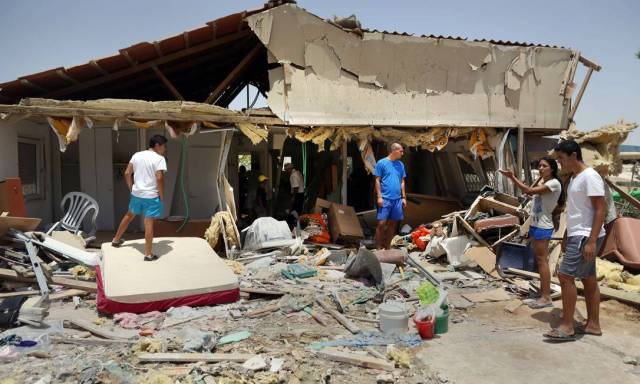 Beersheba residents inspect damage to a house on July 12, 2014, after it was hit by a rocket fired by Palestinian terrorists in the Gaza Strip. Without the Iron Dome, hundreds of houses in Israel would have looked like this. (AP/Menahem Kehana)