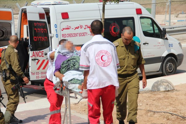 IDF officers escort an injured Palestinian woman for treatment at the IDF field hospital on the Israeli side of the Erez border crossing with the Gaza Strip on July 21, 2014. (IDF/Flickr)