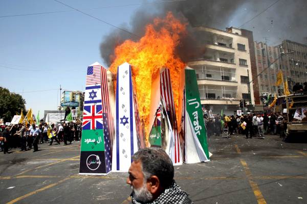 """Iranian demonstrators burn symbolic structures of its archenemies depicting the flags of the U.S., Britain, Saudi Arabia , Islamic state and Israel during a rally marking the international al-Quds (Jerusalem) Day in Tehran July 10, 2015. The green banner reads, """"Saud family,"""" referring to the royal family of Saudi Arabia. REUTERS/Stringer/TIMA"""