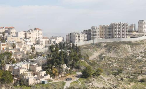 "One facing the other: the houses of French Hill sloping downward from the left face the houses of Anata; between them is the separation fence and the road to Maale Adumim. The fence has not prevented tens of thousands of Arabs from migrating to the ""Israeli side."" (Photograph: Ariel Shragai)"