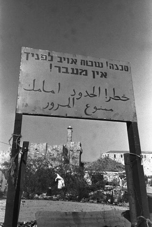 "From 1948 to 1967 the city, before being unified, was divided by walls, wire fences, and signs like this one, which says ""Danger! Enemy Territory Ahead! No Entry!"" In the picture: a view from west Jerusalem into east Jerusalem, July 1951. (Government Press Office)"