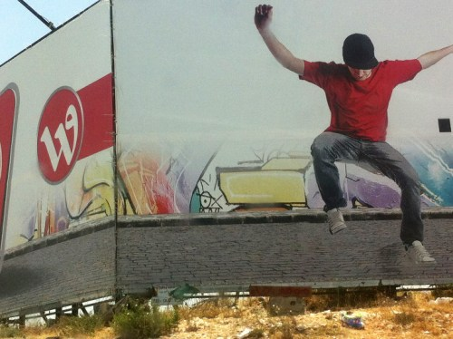 A Palestinian hopping over the fence into Israel.