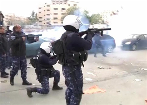 Palestinian security forces firing tear gas into the crowd