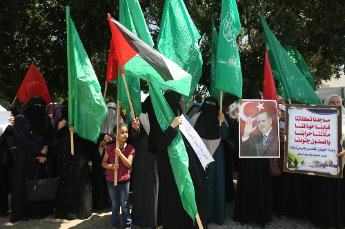 Palestinian supporters of the Hamas movement hold portraits of Turkish President Recep Tayyip Erdogan