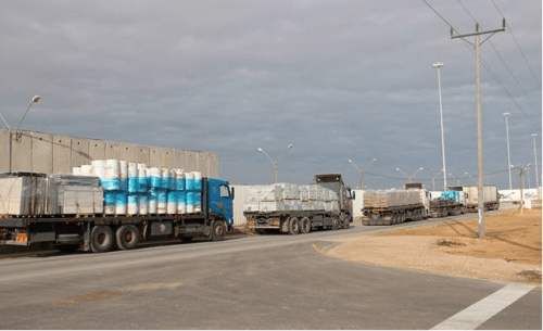 Trucks carry goods at the Kerem Shalom crossing
