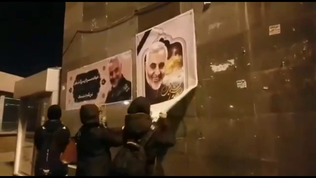 people tear down posters of Soleimani