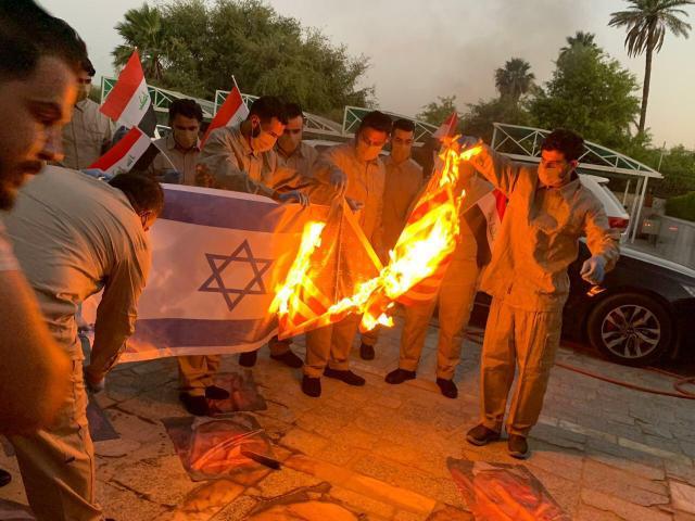 Pro-Iranian militiamen burning the U.S. and Israeli flags