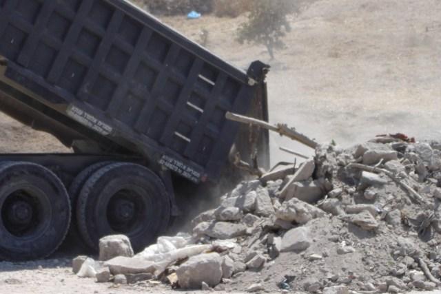 A truck unloads earth