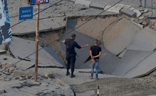 People stand on a collapsed Hamas military tunnel