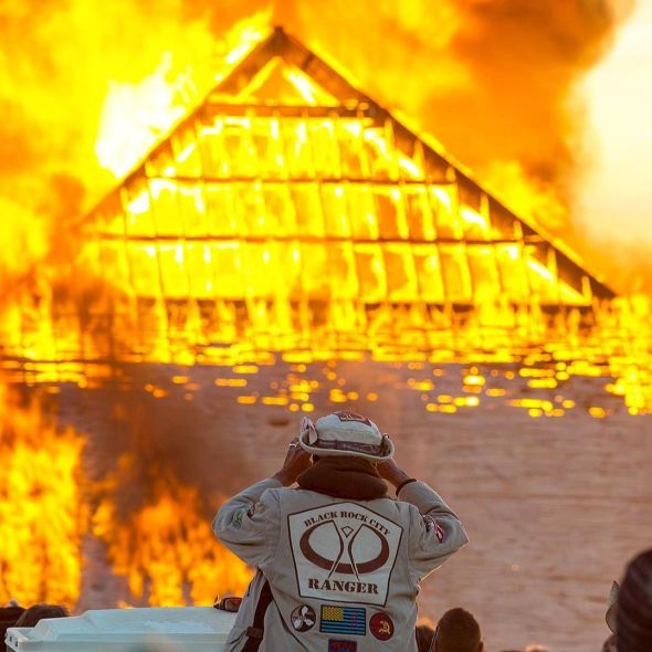 Catacomb of Veils pyramid set ablaze while a BRC ranger looks on.