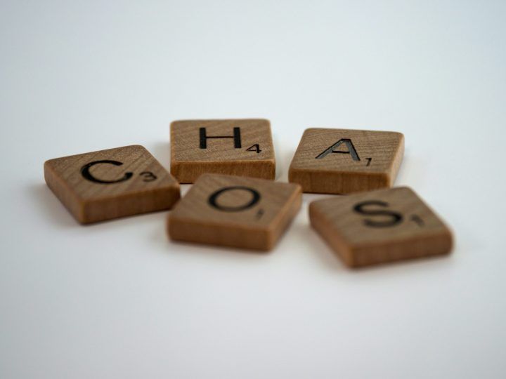Brown wooden letters spell CHAOS | Coping - J. Dakar