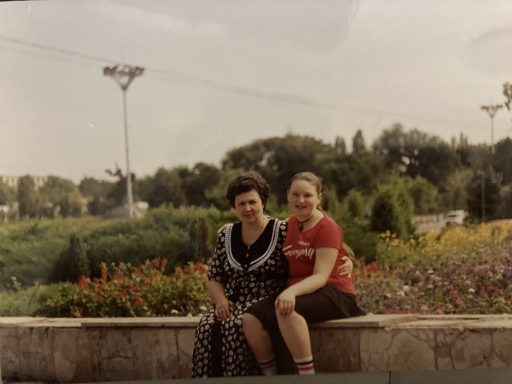 Marina and her mother, visiting Moldova in 1995. They sit on a bench with the countryside in the background.
