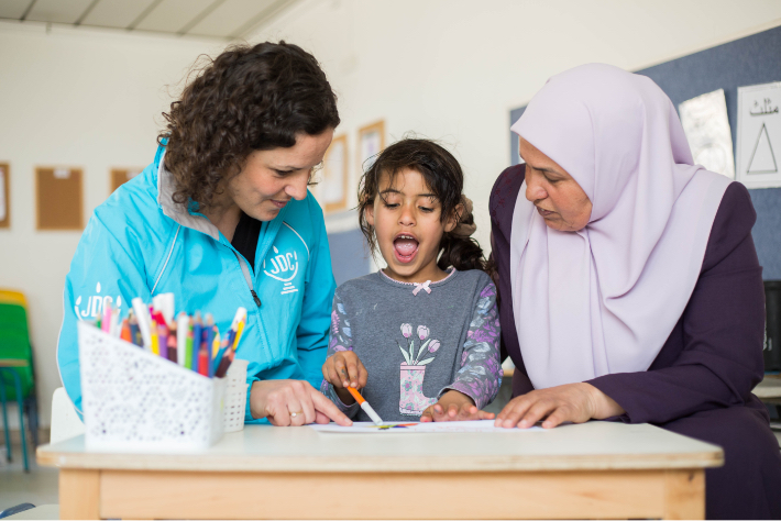 JDC volunteer teaches young Israeli Arab girl to read.